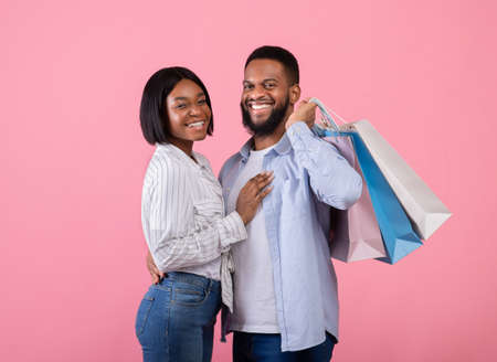 Valentines shopping concept. Smiling black guy and his girlfriend with gift bags on pink studio background. Affectionate sweethearts buying presents for lovers holiday together