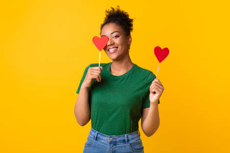 Blinded By Love. Portrait of smiling positive african american woman holding two red paper hearts in hands posing over yellow studio background, lady covering one eye, looking and smiling at camera