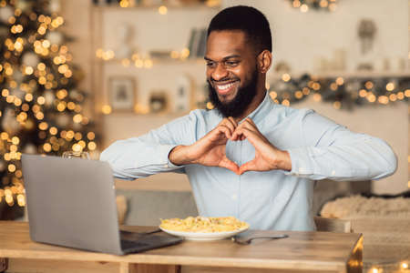 Love And Care. Portrait of smiling african american man making video conference while having dinner, showing heart sign gesture with hands to webcam. Guy sitting at dining table, eating pasta