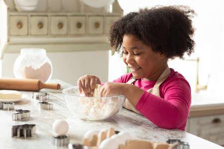 Adorable Little Black Girl Kneading Dough For Cookies, Having Fun In Kitchen Interior. Cute African American Child Enjoying Cooking And Making Homemade Pastry, Side View, Closeup Shot