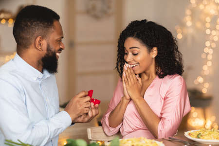 Marry Me. Smiling bearded african american guy holding and showing open box, offering marriage ring to his surprised excited fiance, getting engaged in restaurant or at home at romantic dinner