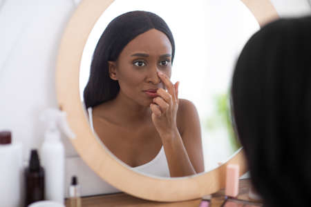 Problem skin during menstruation, acne, pimples and hyperandrogenism. Sad young african american woman looks in mirror and unhappy with big pores on nose at home in interior of bedroom in morning