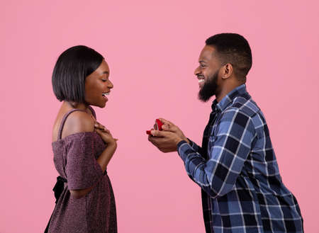 Side view of handsome black guy proposing to his sweetheart, giving her diamond engagement ring on pink studio background. Excited millennial woman happy to marry her beloved man
