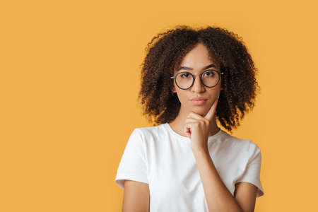 Human face expressions, emotions serious confident. Nice attractive charming creative pensive pensive young african american lady in glasses touch chin, look at camera, isolated on yellow background Banco de Imagens