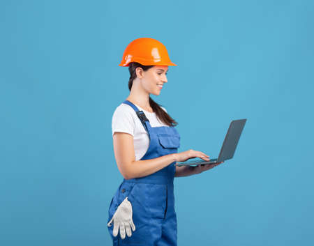 Beautiful Young Female Maintenance Worker Using Laptop, Ordering Construction Materials Online. Lady In Hardhat Making Repair Tools Shopping In Internet, Standing On Blue Background, Copy Space