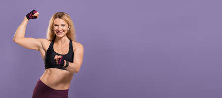 Do your best, fit body, challenge and your choice. Happy middle aged female in sportswear shows biceps and points finger to camera, isolated on purple background, studio shot, panorama, free space