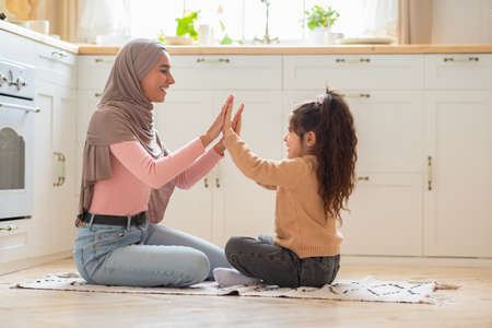 Young muslim mom playing with her little daughter on the floor in kitchen, having fun together at home. Joyful islamic mommy and child having happy family moments, celebrating mothers day, side view Foto de archivo