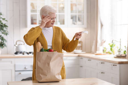 Shocked elderly woman with paper bag with food checking grocery bill and touching her head, standing alone in kitchen, copy space. Old lady got upset with high prices for grocery