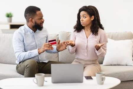 Stressed unhappy black couple arguing about huge expenses, angry man holding credit card blaming woman of overspending debt, family having conflict fight about wasting money. Financial problem at home