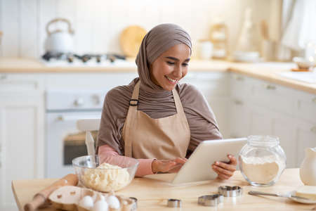 Cheerful Muslim Lady In Hijab Using Digital Tablet In Kitchen, Browsing Cooking Website Or Blog, Checking Dough Recipe Online While Preparing Pastry At Home, Enjoying Making Homemade Food, Free Space