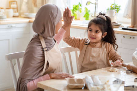 Cheerful Muslim Mom And Daughter Giving High Five To Each Other While Baking In Kitchen. Happy Islamic Family Preparing Homemade Food, Having Fun And Enjoying Spending Time Together At Home, Closeup