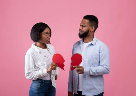 Displeased black guy and lady holding halves of torn paper heart on pink studio background. Upset African American couple getting separated, going through divorce or breakup