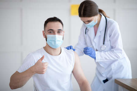 Get vaccinated. Young Caucasian guy showing thumbs up during coronavirus vaccination at clinic, promoting covid-19 immunization. Protection against global virus concept