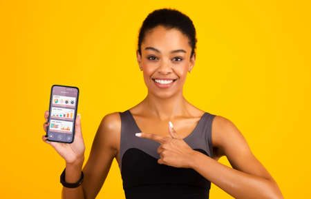 Sporty African Woman Showing Mobile Phone With Jogging App Recommending Running Application For Sport Trainings Over Yellow Studio Background, Smiling To Camera Archivio Fotografico