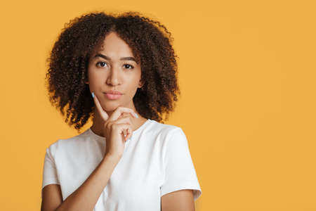 Dreamy nice, pretty, cute lady, youth model touch chin, thought choose decide solve problems, dilemmas. Pensive african american woman, contemplates about, isolated on yellow background, free space