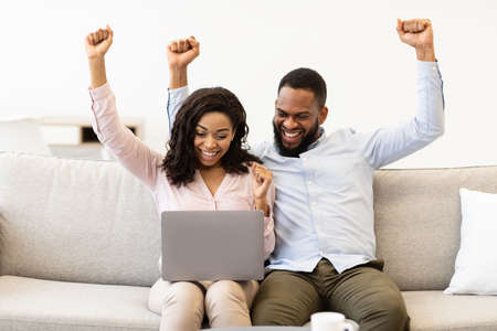 Celebrating Success. Overjoyed african american man and woman happy with money win, satisfied about success. Black couple shaking fists and looking at laptop computer, sitting on the couch at home