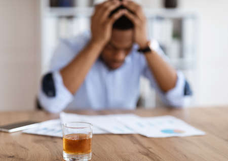 Selective focus on glass of alcohol whiskey over drunk african american office manager or businessman in formal clothes reading documents, holding head. Stressed businessman, alcohol addiction concept Reklamní fotografie