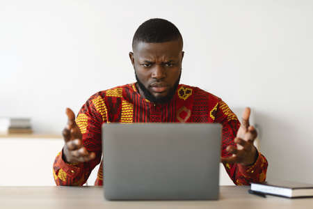 Computer Problems. Frustrated African Businessman In Traditional Clothes Having Troubles With Laptop In Office, Black Guy In Ethnic Shirt Raising Hands Emotionally Reacting To Bad Internet Connection