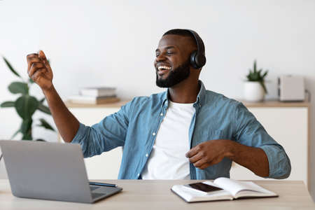 Work With Fun. Cheerful Black Freelancer Man In Wireless Headphones Listening Music And Playing Virtual Guitar At Workplace, Resting At Desk In Home Office, Enjoying Remote Job Opportunities