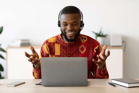 Online Tutoring. Male African Teacher In Headset Having Web Lesson With Laptop, Smiling Black Coach Wearing Traditional Ethnic Shirt, Gesturing And Talking At Camera, Enjoying Distance Training Stock Photo