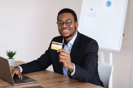 Internet banking for business, e-commerce concept. Happy black businessman using laptop, recommending credit card for online shopping or payments, office interior, copy space