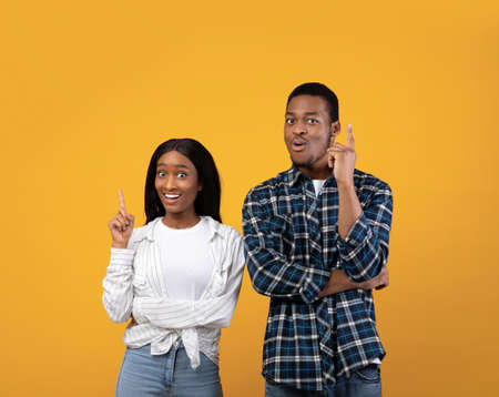 Eureka, inspiration, great solution and good mood. Excited cheerful millennial african american guy and lady point fingers up, making decision, isolated on yellow background, studio shot, free space