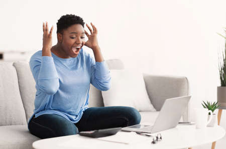 Celebrating Victory. Overjoyed african american curvy woman happy with money win, satisfied about success. Black lady screaming yes and looking at laptop computer, sitting on the couch at home