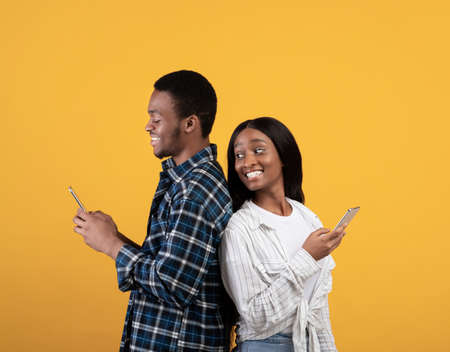 Blogs, social media, unusual message and interesting event. Cheerful young african american lady look over shoulder in smartphone of smiling husband, isolated on yellow background, studio shot