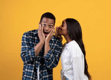 Gossip, unusual proposal, mysteries and surprising event. Millennial african american lady whispering in ear of shocked guy with open mouth, isolated on yellow background, studio shot, free space