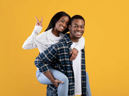 People lifestyle, free time, husband and wife have fun. Smiling millennial african american man hold woman on back, lady show peace sign with hand, isolated on yellow background, studio shot