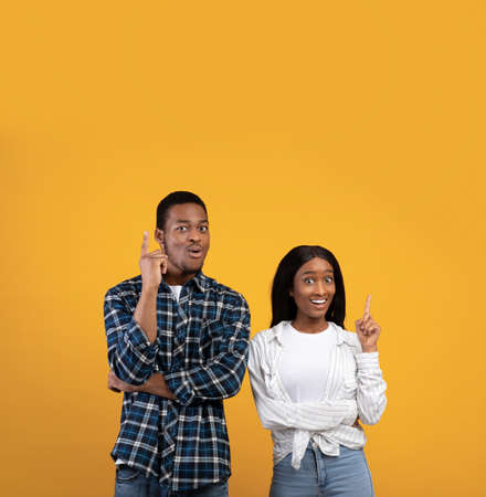 Got an idea, solution and facial emotions of people. Excited joyful young african american couple point fingers up, making decision, isolated on yellow background, studio shot, square, free space