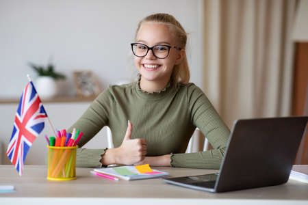 Cheerful girl teenager with flag of Great Britain showing thumb up, using laptop, having educational online course, studying english on Internet, home interior. English classes online concept