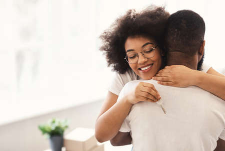 Family Housing Concept. Happy African Couple Holding New House Key Embracing Celebrating Moving Apartment Standing Indoors. Real Estate Owners. Copy Space