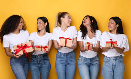 Joyful Mixed Ladies Posing With Gifts Holding Wrapped Present Boxes Celebrating Holiday Standing On Yellow Background. Studio Shot. Celebration, Holidays And Gifts Concept. Banque d'images