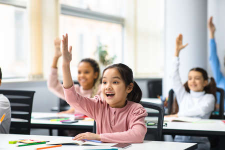 Education, Elementary School, Learning and People Concept. Diverse group of smart junior school kids sitting at desks in classroom and raising hands for an answer, studying with pleasure