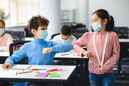 Stop Spreading Virus Concept. Small diverse schoolchildren wearing protective face masks greeting each other and bumping elbows at classroom. Boy sitting at desk, girl standing with backpack Banco de Imagens - 162640249