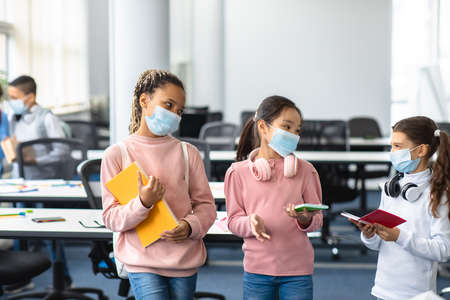 Healthcare And Education Concept. Diverse group of international schoolgirls wearing disposable surgical masks standing with notebooks and headphones in classroom and talking. Lifestyle, Communication