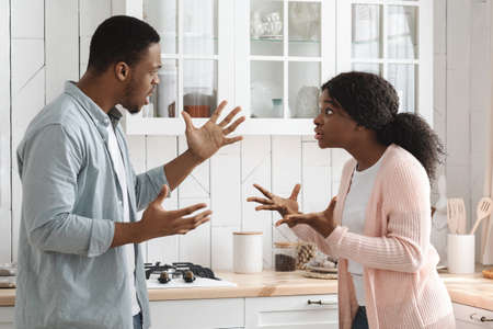 Relationship Problems. Young African American Couple Arguing In Kitchen, Shouting And Blaming Each Other, Black Millennial Spouses Quarreling At Home, Suffering Marital Crisis, Side View, Free Space