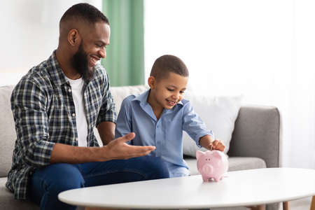 Personal Savings. African Father And Son Putting Coin In Piggybank Sitting On Sofa At Home, Dad Teaching His Kid Financial Literacy, Talking About Money And Budget Planning. Selective Focus