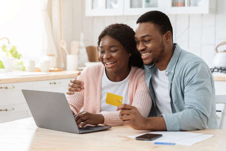 Online Payment. Black Spouses With Laptop And Credit Card In Kitchen Paying Utilities Or Shopping In Internet, Young African American Couple Using Computer And E-Banking At Home, Free Space