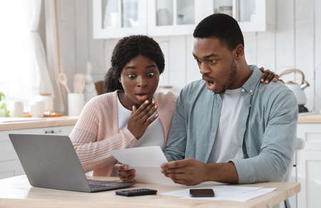 Shocked black couple in kitchen stressed with financial problems, doing calculations of family budget together. Frustrated african american spouses sitting at table looking at loan documents