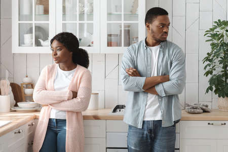 Relationship Crisis. Offended Young Angry African American Spouses Standing In Kitchen After Quarrel, Ignoring Each Other, Black Millennial Couple Suffering Misunderstanding In Relations, Free Space