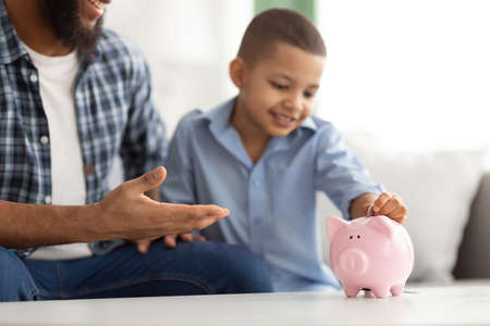 Personal Savings. Black Dad And Son Putting Coin In Piggybank Sitting At Home. Young Father Teaching His Child Financial Literacy And Budget Planning. Selective Focus On Piggy Bank, Cropped