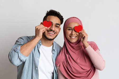 Valentines Day Concept. Loving Muslim Couple Holding Red Paper Hearts Near Eyes And Smiling At Camera, Romantic Arab Man And Woman In Hijab Having Fun Over Grey Studio Background, Free Space