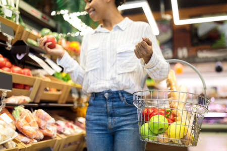 African American Woman Doing Grocery Shopping In Supermarket. Cropped, Selective Focus On Basket Full Of Organic Fruits And Vegetables. Unrecognizable Female Customer Choosing Natural Healthy Food 免版税图像