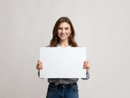 Beautiful Young Woman Holding Blank Placard With Copy Space For Advertisement. Smiling millennial lady demonstrating white empty billboard with place for text, standing over grey studio background Imagens