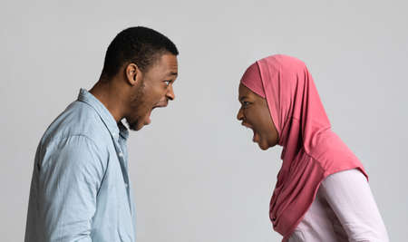 Side view of angry black muslim couple yelling at each other on grey studio background, panorama. Furious african american lady in headscarf having fight with boyfriend or husband
