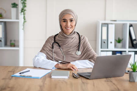 Portrait of smiling female doctor young beautiful woman in hijab with stethoscope posing in her cabinet, sitting at workdesk with medical chart, notebook and laptop in clinic, copy space Stockfoto