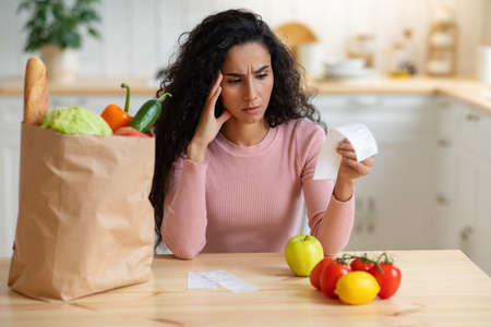 Grocery Expenses. Concerned Brunette Woman Sitting At Table In Kitchen, Looking At Bill After Food Shopping, Millennial Lady Upset About Prices, Suffering Financial Crisis And Poverty, Free Space