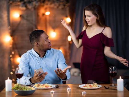 Furious Young Woman Blaming Her Black Boyfriend For Using Smartphone During Romantic Dinner. Young Interracial Couple Emotionally Arguing At Valentines Day Date In Restaurant, Free Space